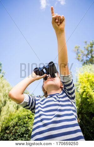 Low angle view of a child looking something with binoculars and pointing on a park