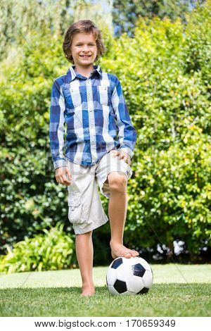 Cute boy smiling and posing with his foot on a soccer ball on a park