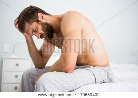 Depressed man on bed with hand on head at bedroom
