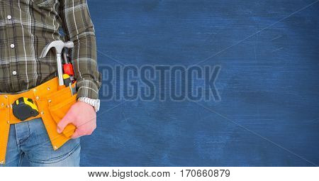 Mid section of handyman standing with worktools against blue background