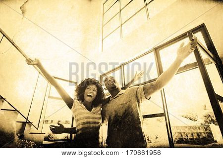 Grey background against excited young couple in their new home
