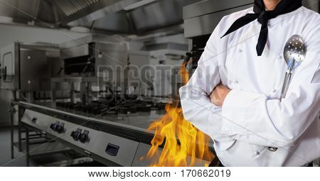 Mid section of chef standing with arms crossed in kitchen of restaurant