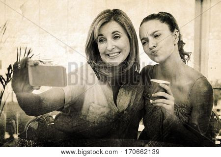 Grey background against mother taking selfie while daughter puckering