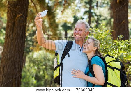 Couple smiling and taking a photo on the wood