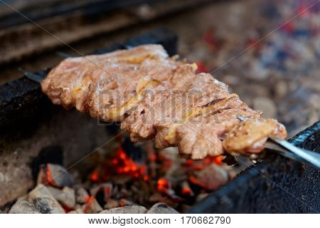 Spit roasted lamb meat on charcoal grill in a restaurant