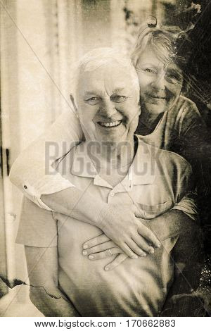 Grey background against portrait of happy senior couple at home