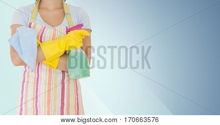 Mid section of woman holding spray bottle and napkin against blue background