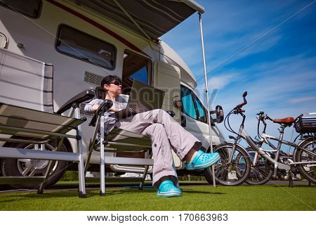 Woman sitting on a chair near the camper and looking at a laptop. Caravan car Vacation. Family vacation travel, holiday trip in motorhome