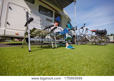 Woman resting on a chair on the nature. Caravan car Vacation. Family vacation travel, holiday trip in motorhome