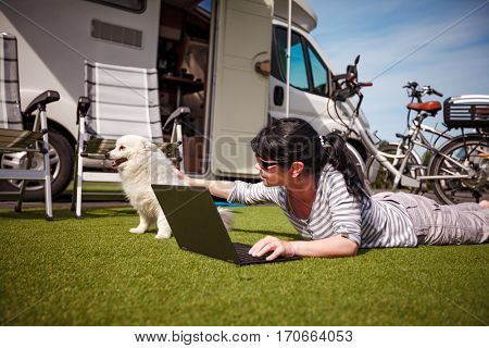 Woman on the grass with a dog looking at a laptop. Caravan car Vacation. Family vacation travel, holiday trip in motorhome