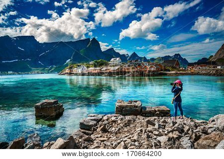 Nature photographer tourist with camera shoots Lofoten archipelago islands Norway. Beautiful Nature Norway.