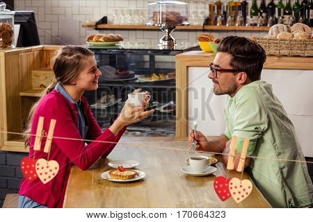 Couple interacting with each other while having coffee in cafeteria