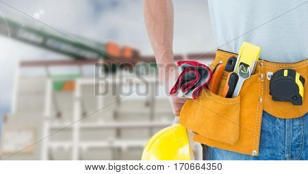 Mid section of construction man with tools at site