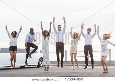 Well dressed people jumping next to a limousine on a night out