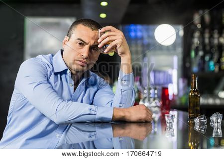 Depressed man drinking alcohol in a pub