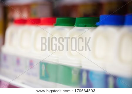 Milk bottles tidied in shelf at grocery store