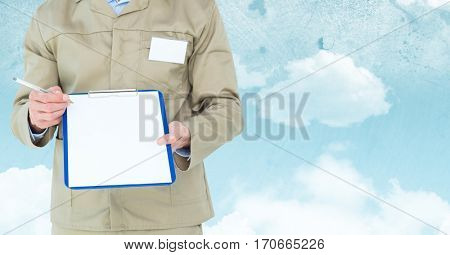 Mid section of delivery man standing with clipboard against sky background