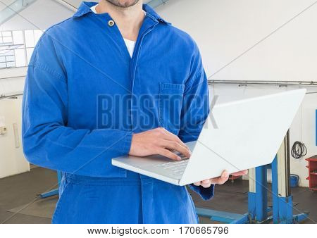 Mid section of mechanic using laptop in workshop