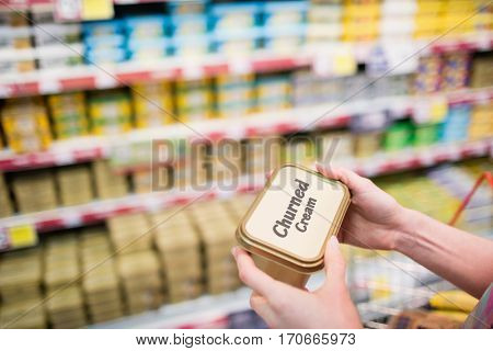 Close up view of hands holding churned cream at supermarket