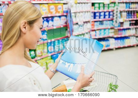 Over shoulder view of woman looking product at supermarket