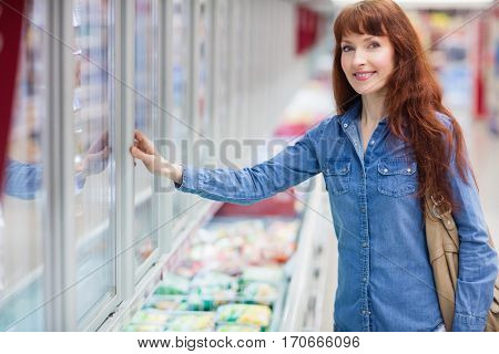 Woman smiling at camera while doing grocery shopping in frozen section