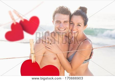 Composite image of couple embracing each other at beach with hanging hearts around