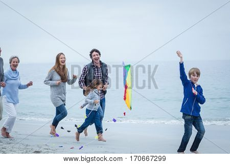 Cheerful multi-generation family running at sea shore against sky