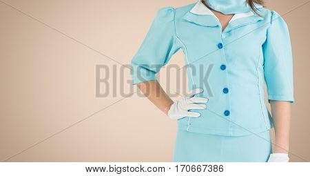 Mid section of air hostess standing with hands on hip against beige background