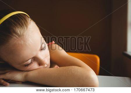 Schoolchild sleeping on desk at school