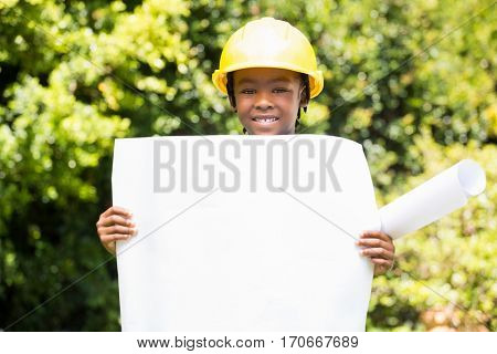 Boy dressed as an architect holding a plan in the park