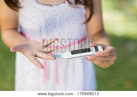 Close-up of girl testing diabetes on glucose meter in park