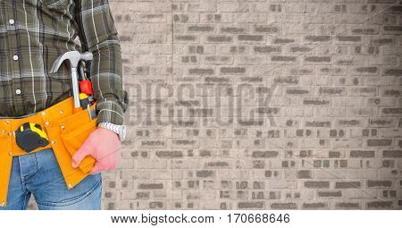 Mid section of handyman with tool belt around his waist against brick wall