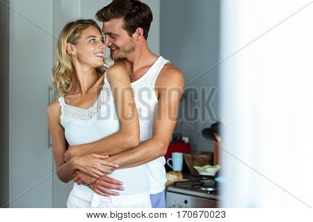 Romantic young couple embracing while looking at each other in kitchen at home