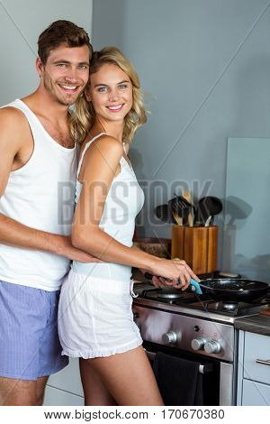 Portrait of romantic young couple cooking food in kitchen at home