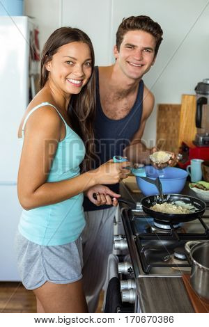 Portrait of smiling young couple cooking food in kitchen at home