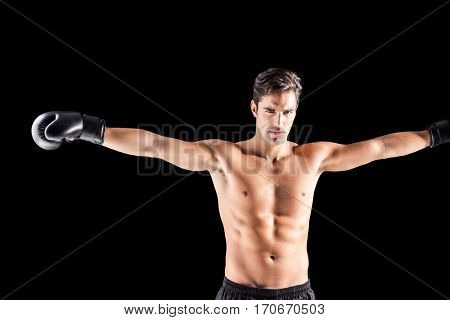 Boxer standing with arms outstretched on black background