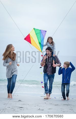Full length of happy family with kite enjoying at sea shore