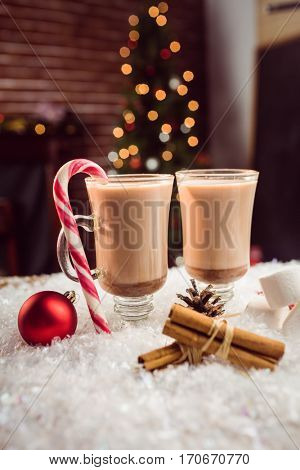 close up view of composite image of hot chocolates against Christmas tree background