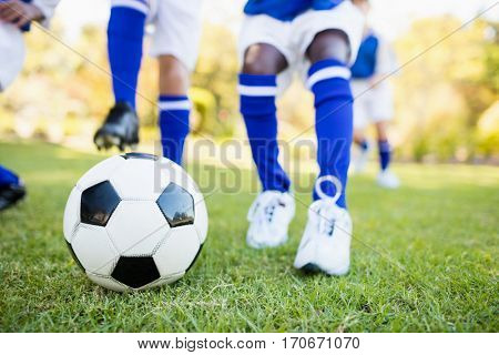 Close up view of children playing soccer in park