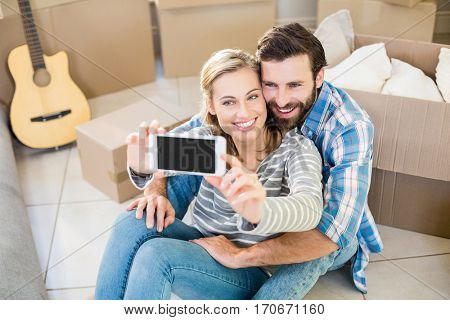 Couple sitting on floor and taking selfie at home
