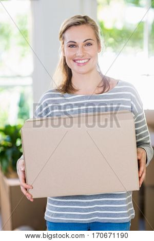 Portrait of young woman holding cardboard boxes in their new house