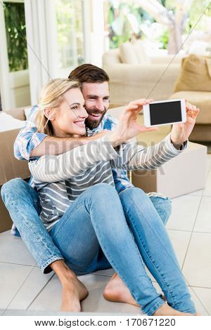Couple sitting on floor and taking selfie in living room at home