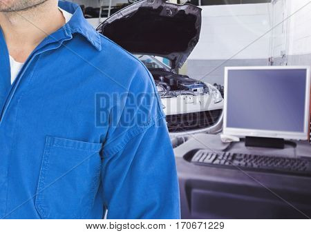 Mid section of mechanic with computer in background at garage