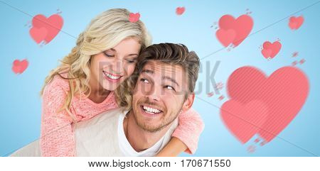 Handsome man giving piggy back to his girlfriend against blue background