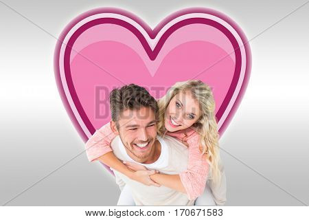 Handsome man giving piggy back to his girlfriend against grey background