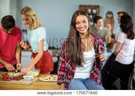 Young woman holding beer bottle with friends at home