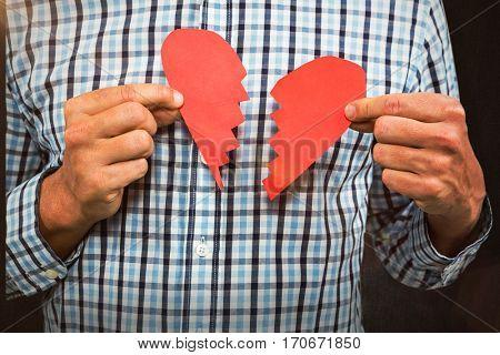 Sad man with broken heart against grey background