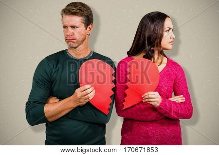 Serious couple holding cracked heart shape against grey