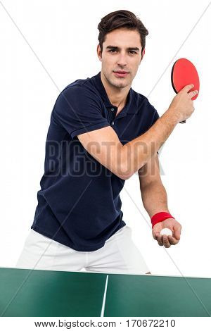 Confident male athlete playing table tennis on white background