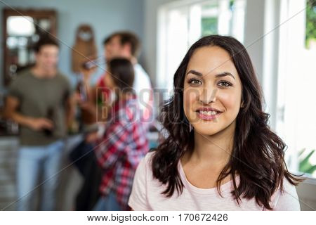 Portrait of happy woman with friends enjoying at home